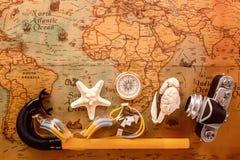 Las cáscaras del mar, una cámara vieja, un compás y los accesorios para la mentira que bucea en un vintage trazan Fotografía de archivo libre de regalías