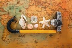 Las cáscaras del mar, una cámara vieja, un compás y los accesorios para la mentira que bucea en un vintage trazan Imágenes de archivo libres de regalías
