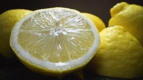 Las ca?das de la gota del jugo de la mitad cutted del lim?n, los limones frescos maduros est?n en la tabla, tiro macro aislado co almacen de video