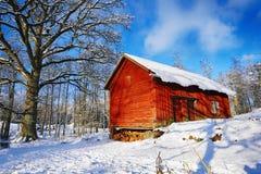 Las cabañas viejas, casas en un invierno nevoso ajardinan Imágenes de archivo libres de regalías