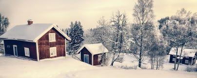 Las cabañas viejas, casas en un invierno nevoso ajardinan Fotografía de archivo libre de regalías