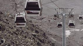 Las cabinas de la elevación de Funitel montan en los cables en montañas pedregosas almacen de metraje de vídeo