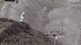 Las cabinas de la elevación de la góndola montan en los cables en montañas pedregosas almacen de metraje de vídeo