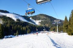 Las cabinas del cablecarril afortunado con la familia de esquiadores en Jasna Low Tatras Foto de archivo