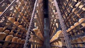 Las cadenas de las bandejas del metal con los conos de helado se están moviendo en direcciones opuestas almacen de video