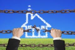 Las cadenas oxidadas del hierro interrumpidas por las manos con la casa se nublan Fotografía de archivo libre de regalías