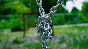 Las cadenas robustas del acero que cuelgan hacia abajo están conectadas en un solo nudo Metal el soporte para una atracción del ` metrajes