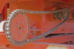 Las cadenas y el engranaje rueda adentro la maquinaria agrícola y la naranja Imagenes de archivo