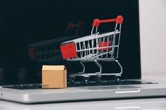 Las cajas adentro y la carretilla en compras en línea del ordenador portátil es una forma de comercio electrónico que permita que foto de archivo