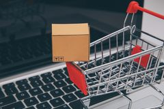 Las cajas adentro y la carretilla en compras en línea del ordenador portátil es una forma de comercio electrónico que permita que imagenes de archivo