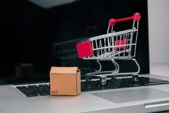 Las cajas adentro y la carretilla en compras en línea del ordenador portátil es una forma de comercio electrónico que permita que imágenes de archivo libres de regalías