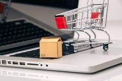 Las cajas adentro y la carretilla en compras en línea del ordenador portátil es una forma de comercio electrónico que permita que imagen de archivo