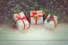 Las cajas blancas adornaron la cinta y el metal rojos Jingle Bell Decoración del día de fiesta de la Navidad Fotos de archivo libres de regalías