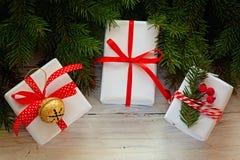 Las cajas blancas adornaron la cinta y el metal rojos Jingle Bell Decoración del día de fiesta de la Navidad Imagenes de archivo