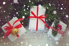 Las cajas blancas adornaron la cinta y el metal rojos Jingle Bell Decoración del día de fiesta de la Navidad Foto de archivo libre de regalías