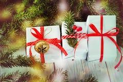 Las cajas blancas adornaron la cinta y el metal rojos Jingle Bell Decoración del día de fiesta de la Navidad Imágenes de archivo libres de regalías