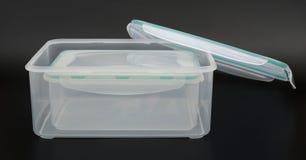 Las cajas de almacenamiento translúcidas con el labio se abrieron en fondo negro Fotografía de archivo libre de regalías