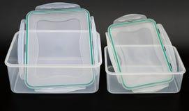 Las cajas de almacenamiento translúcidas con los labios se abrieron en fondo negro Foto de archivo