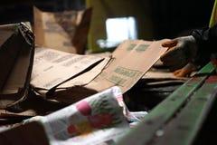 Las cajas de cartón se clasifican a mano en el reciclaje del centro fotografía de archivo