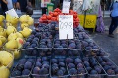 Las cajas de higos, de peras y de tomates redondos púrpuras oscuros deliciosos en mercado de la fruta local atascan el fondo con  Imágenes de archivo libres de regalías