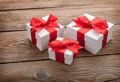 Las cajas de regalo blancas con rojo arquean en el viejo tablero Concepto del regalo Imagenes de archivo