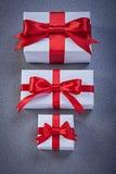 Las cajas de regalo blancas con rojo ataron cintas en días de fiesta superficiales grises imagen de archivo