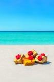Las cajas de regalo con rojo grande arquean en la playa soleada arenosa Fotos de archivo