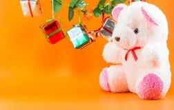 Las cajas de regalo de la Navidad con el peluche refieren el fondo anaranjado Fotografía de archivo libre de regalías