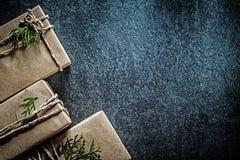 Las cajas de regalo envueltas con thuya ramifican en celebra negro del fondo fotografía de archivo