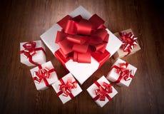 Las cajas de regalo festivas blancas con rojo arquean en una tabla de madera imágenes de archivo libres de regalías