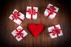 Las cajas de regalo festivas blancas con rojo arquean en una tabla de madera con re foto de archivo