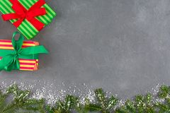 Las cajas de regalo de Navidad en papel rayado del color, cintas, abeto ramifican Imagenes de archivo