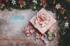 Las cajas de regalo rojas hermosas confinadas con los ornamentos rojos de las ramas del pino, número 2019 en el centro, parte inf imagen de archivo libre de regalías