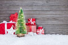 Las cajas de regalo rojas y el pequeño árbol de navidad con día de fiesta se enciende en s Imagen de archivo