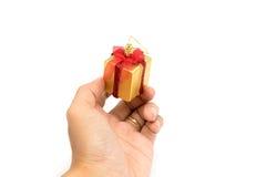 Las cajas de regalo rojo y color oro a disposición dan para usted en el fondo blanco Fotografía de archivo libre de regalías