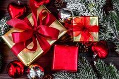 Las cajas de regalos con el abeto ramifican en la opinión superior del fondo de madera Foto de archivo libre de regalías