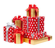 Las cajas rojas y rayadas y del oro con los regalos ataron arcos en blanco Fotografía de archivo