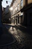 Las calles cobbled de la ciudad europea vieja por la mañana Reflexiones en el pavimento riga foto de archivo