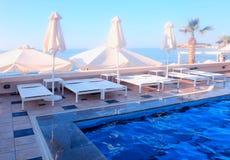 Las camas al aire libre del sol acercan a la piscina en centro turístico de verano Imágenes de archivo libres de regalías