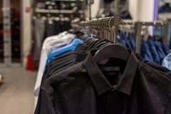 Las camisas de los hombres negros, azules y blancos en las suspensiones dentro de la tienda, primer con un fondo borroso imagenes de archivo