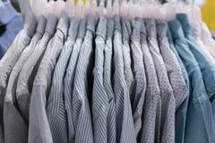Las camisas en suspensiones se cierran para arriba Camisas en perchas imagen de archivo