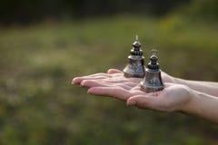 Las campanas budistas están en la palma abierta Imagenes de archivo
