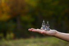 Las campanas budistas están en la palma abierta de la mano del ` s de las mujeres Imágenes de archivo libres de regalías