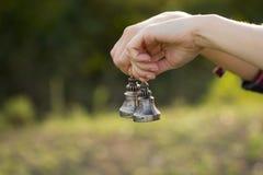 Las campanas budistas están en la palma abierta de las manos del ` s de las mujeres Primer Imagen de archivo