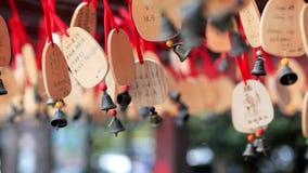 Las campanas de madera con deseos cuelgan y se mueven desde el viento Hainan, China Clouse para arriba Belces en cintas rojas metrajes