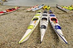 Las canoas coloridas mienten en rocas cerca del agua Fotografía de archivo libre de regalías