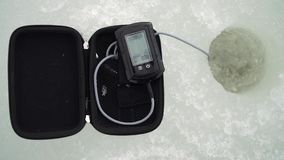 Las capturas del pescador pescan con un receptor acústico de eco del invierno en un agujero en un río almacen de video