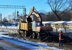 Las cargas del excavador machacaron de piedra en un cuerpo del camión volquete Construcción del ferrocarril Preparación de la sup fotografía de archivo libre de regalías