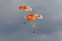 Las cargas en los paracaídas van abajo de la tierra Imagenes de archivo