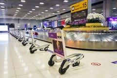 Las carretillas se ponen en orden en la correa de la demanda de equipaje imagen de archivo libre de regalías